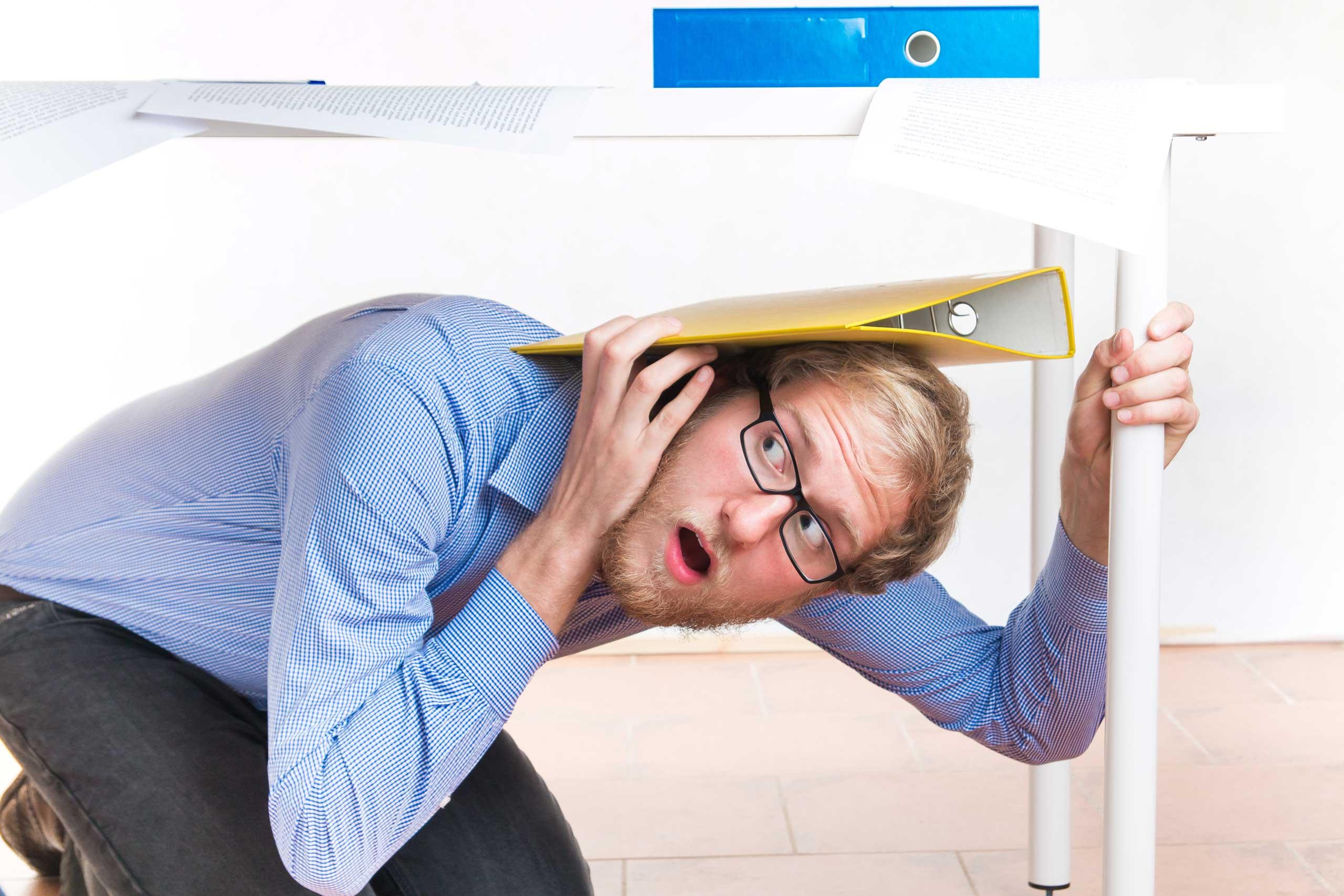 business man hiding under a desk